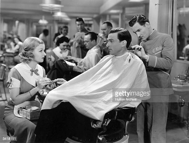 Walter Pidgeon relaxes in the barber's chair while Joan Bennett gives him a manicure in a scene from the Paramount film 'Big Brown Eyes' directed by...