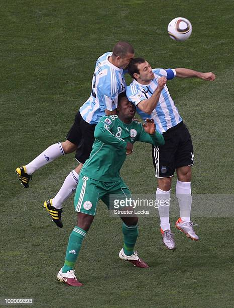 Walter Samuel and Javier Mascherano of Argentina battle for the ball with Yakubu Ayegbeni of Nigeria during the 2010 FIFA World Cup South Africa...