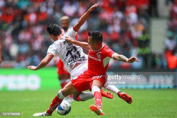 Walter Sandoval of Chivas struggles for the ball with Rodrigo Salinas of Toluca during the third round match between Toluca and Chivas as part of the...