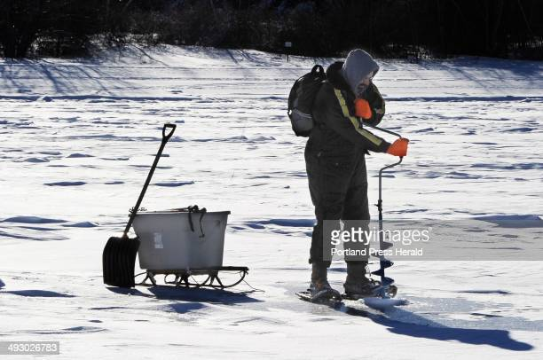 Walter Selens from Gorham uses a hand auger to cut a hole for a ice trap as early ice on Sebago Lake brings out ice fishermen at Lower Bay in...