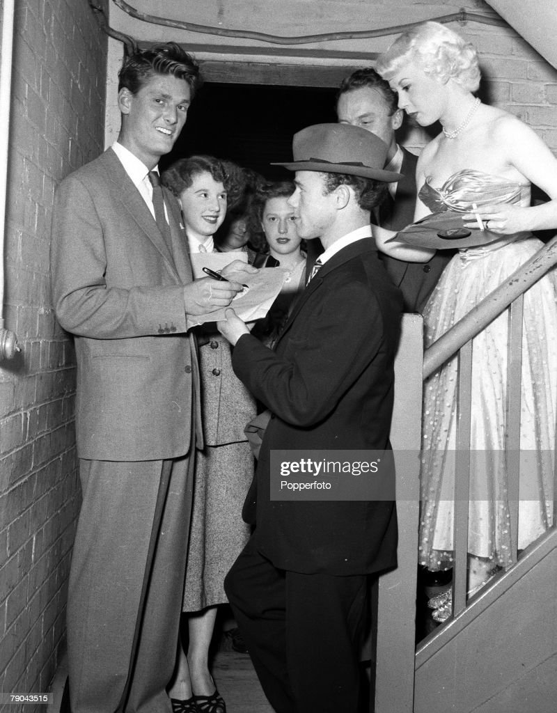 """1954. Walthamstow, London. Radio Luxembourg Disc Jockey Peter Murray is pictured signing an autograph for a """"Teddy"""" boy at the Granada Cinema watched by Billie Anthony (right). : News Photo"""