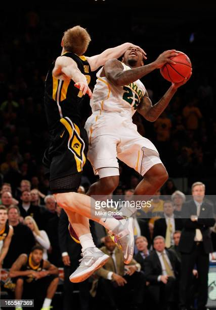 J Walton of the Baylor Bears drives to the net as Mike Gesell of the Iowa Hawkeyes defends during the 2013 NIT Championship at Madison Square Garden...