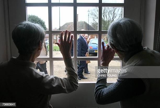 Two residents wave to Britain's Prince Charles during his tour of Whiteley Village in WaltononThames Surrey 23 March 2007 The Prince was visiting the...