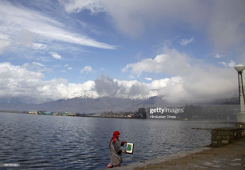 A waman collecting water on the banks of Dal Lake as a brief sunshines dazzled the eyes after getting reflected from the snow covered mountains of Zabarwan range overlooking Dal Lake, on February 5, 2013 in Srinagar, India. Since Sunday night, Kashmir has been lashed with intermittent snow and rain which weather office predicted will continue for two more days.