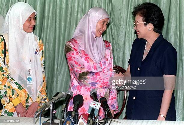Wan Azizah Wan Ismail wife of jailed former Malaysian deputy prime minister Anwar Ibrahim shakes hands with former Philippine president Corazon...
