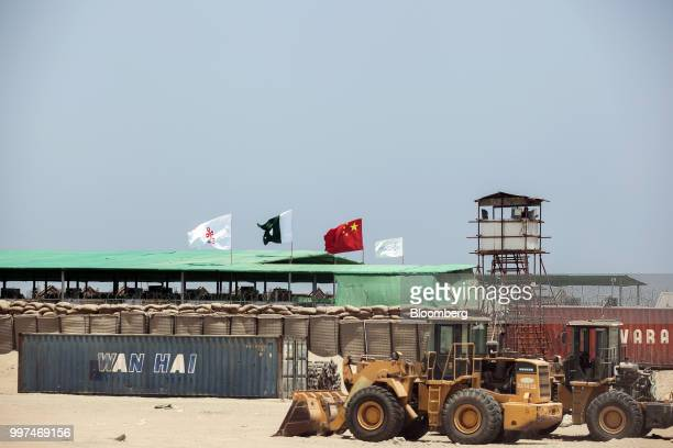 A Wan Hai Line Ltd shipping container sits beyond an excavator outside a workers camp operated by China Overseas Ports Holding Co in Gwadar...