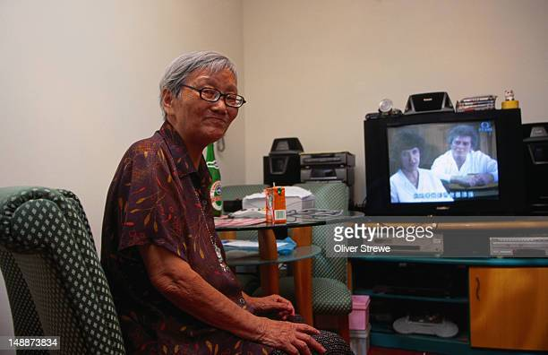 Wan Lau's mother watching tv in the diningroom of Wan Lau's tiny two bedroom apartment, Kwai Fong area.