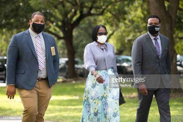 Wanda CooperJones mother of Ahmaud Arbery center walks to the Glynn County Courthouse with attorney Lee Merritt right and chief investigator Charles...