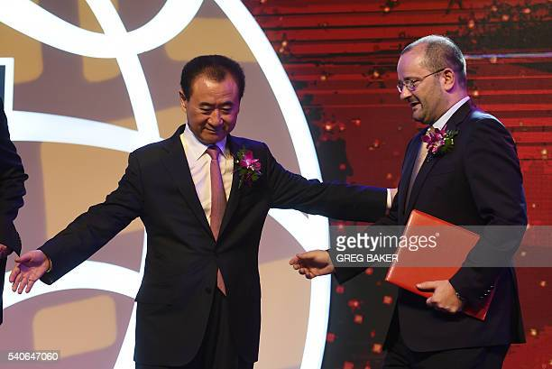 Wanda Group chairman Wang Jianlin leads the way for FIBA secretary general and IOC member Patrick Baumann after the announcement of a business...