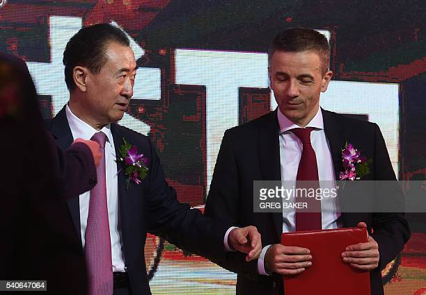 Wanda Group chairman Wang Jianlin walks with Philippe Blatter, president and CEO of Wanda Sports Holdings, after the announcement of a business...