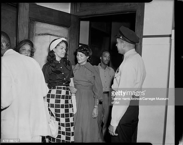 Wanda Jackson Mrs John Hicks Elmer Taylor and police officer John Hicks standing in hallway Pittsburgh Pennsylvania June 15 1949