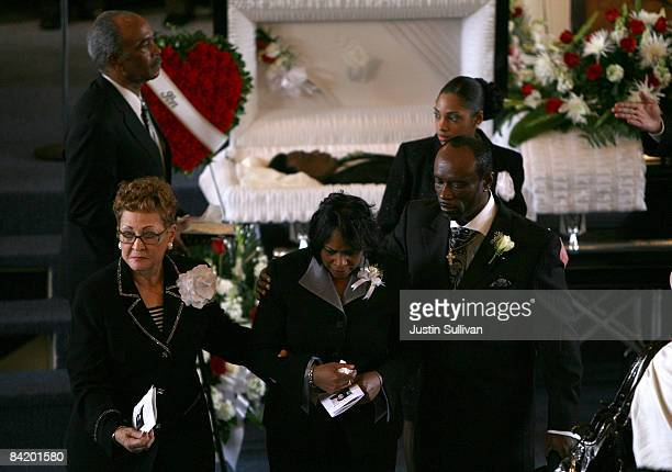 Wanda Johnson mother of twenty two yearold Oscar Grant III is escorted by unidentified people as she walks away from his coffin during a funeral...