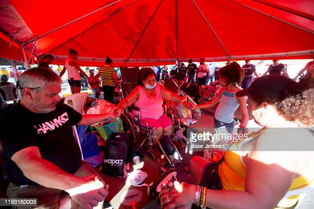 Wanda Santana prays along members pf her familiay at the refugee camp located at the Mariano Rodríguez Coliseum on January 11 2020 in Guanica Puerto...