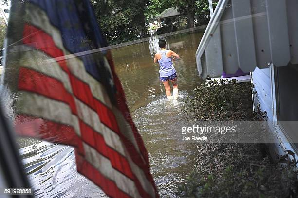 Wanda Sittig walks through the flood waters around her father's home as she helps salvage what she can on August 19, 2016 in St Amant, Louisiana....
