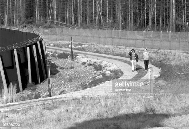 Wanderer auf dem Kolonnenweg entlang am Metallgitterzaun der DDRGrenzanlagen im Oberharz im Grenzgebiet der innerdeutschen Grenze zwischen...