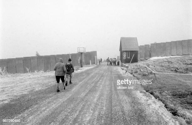 Wanderer auf dem Weg zu einem Durchlaßtor in der Mauer die den Brocken sidchert aufgenommen im Januar 1990 Der Brocken im Harz war bis zur deutschen...