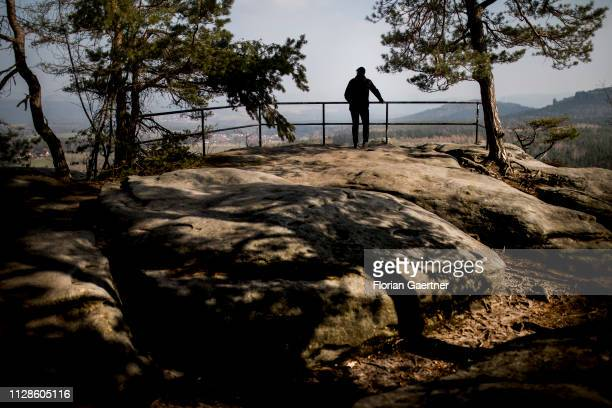A wanderer is pictured on the top of the 'Pfaffenstein' on February 28 2019 in Pfaffendorf Germany