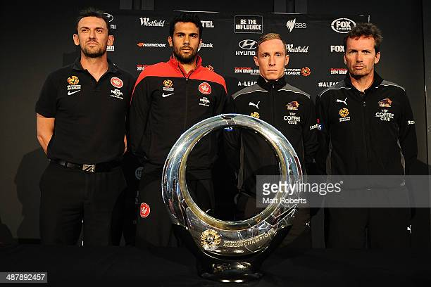 Wanderes coach Tony Popovic and Nikolai ToporStanley of the Wanderers pose with the champions trophy with Matthew Smith of the Roar and Roar coach...