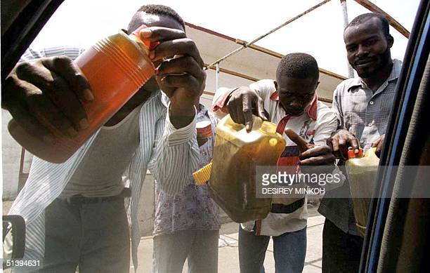 """Wandering petrol sellers known as """"Kaddhafi"""" offer their products 31 January 2001 in Kinshasa. Despite the illegality they sell black market petrol,..."""