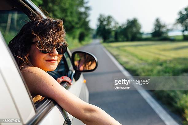 Wanderlust girl traveling by car in summer time