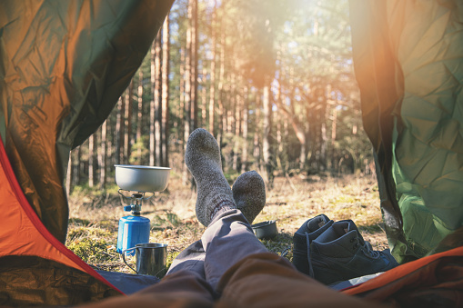 wanderlust outdoor camping - traveler feet out of the tent 1139849077