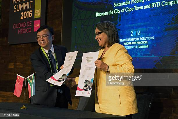 Wang Chuanfu president of BYD Co and Patricia de Lille mayor of Cape Town hold up signed Sustainable Mobility Partnership agreements during the C40...