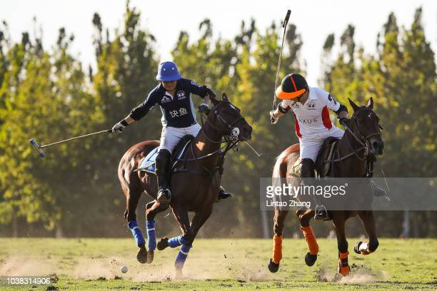 Wang Gang of Team AXUS hits the ball with Li Yanyang of Team Fast Fish during the 2018 China Elite Polo Tournament Argentine Republic Polo Cup match...