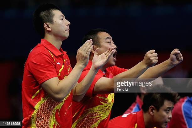 Wang Hao Ma Long and coach Liu Guoliang of China celebrate during Men's Team Table Tennis first round match against team of Russia on Day 8 of the...