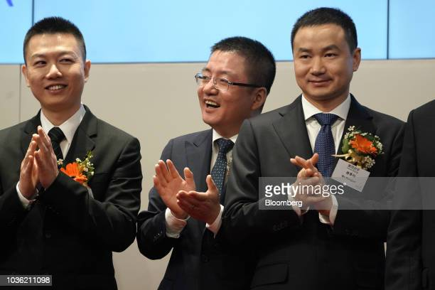 Wang Huiwen senior vice president and cofounder of Meituan Dianping center and Mu Rongjun senior vice president and cofounder right applaud during...