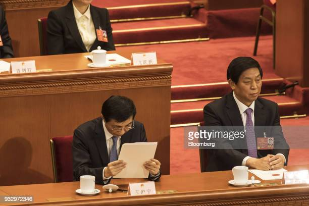 Wang Huning member of the Communist Party of China's Politburo Standing Committee left reads a document as Li Zhanshu member of the Communist Party...