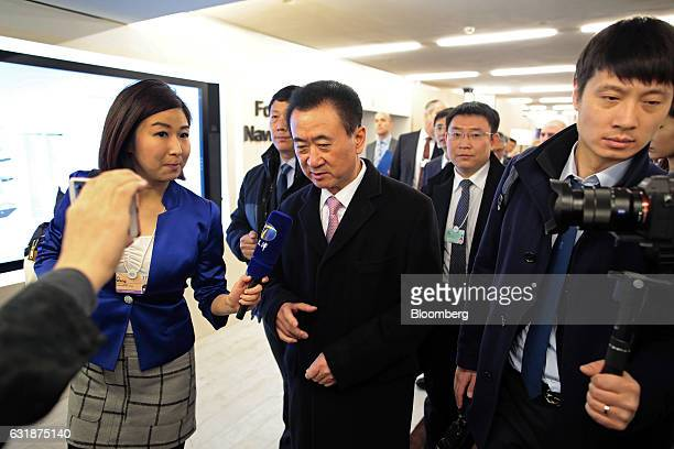 Wang Jianlin, billionaire and chairman and president of Dalian Wanda Group Co., center, speaks to the media between sessions during the World...