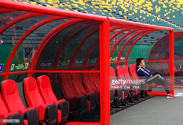 Wang Jun of China PR sits in the bench area prior to their match against Germany at Commonwealth Stadium on August 8 2014 in Edmonton Canada