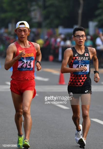 Wang Kaihua of China and Toshikazu Yamanishi of Japan compete in the men's 20km walk race competition during the 2018 Asian Games in Jakarta on...