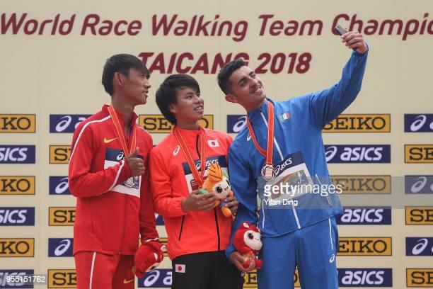 Wang Kaihua of China Koki Ikeda of Japan and Massimo Stano of Italy take a selfie during medal ceremony of Men's 20 kilometres Race Walk of IAAF...