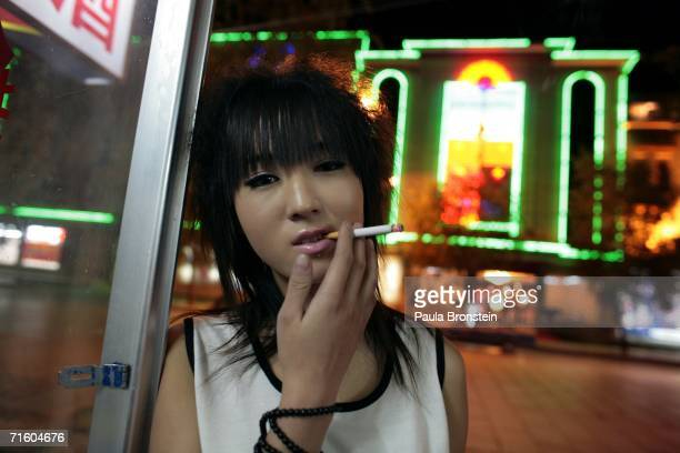 Wang Lili age 17 an alleged sex worker waits for business across the street from a nightclub August 5 2006 in a new section of Lhasa in the Tibet...