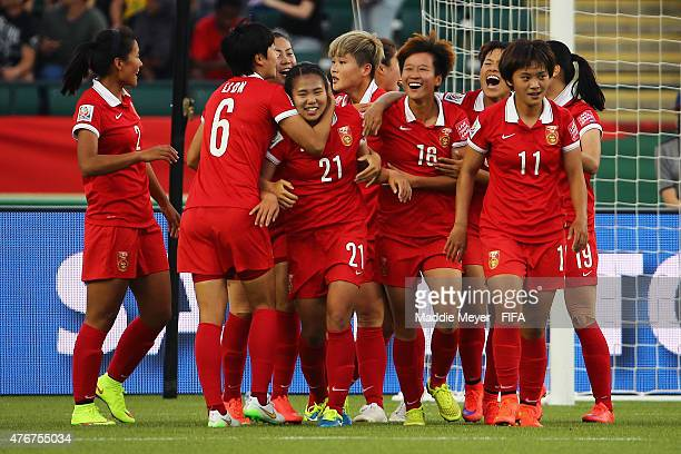 Wang Lisi of China PR is swarmed by teammates after scoring the game winning goal against the Netherlands during the FIFA Women's World Cup Canada...