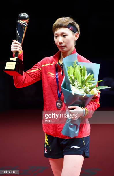 Wang Manyu of China celebrates with her trophy during awarding ceremony after winning women's singles final match against Ding Ning of China on day...