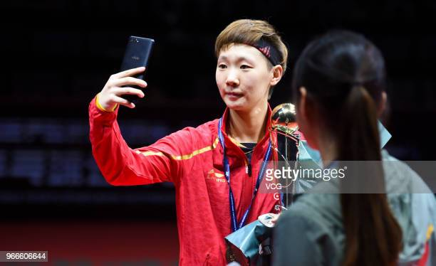 Wang Manyu of China takes a selfie with her trophy during awarding ceremony after winning women's singles final match against Ding Ning of China on...