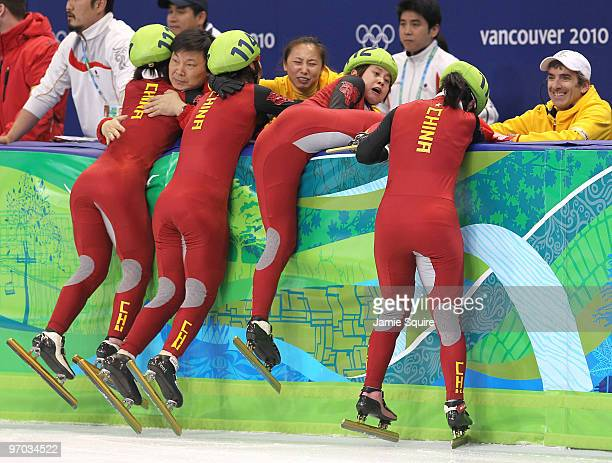 Wang Meng of China cuts the face of teammate Zhang Hui with the blade of her ice skate after Team China won the gold medal in the Short Track Speed...