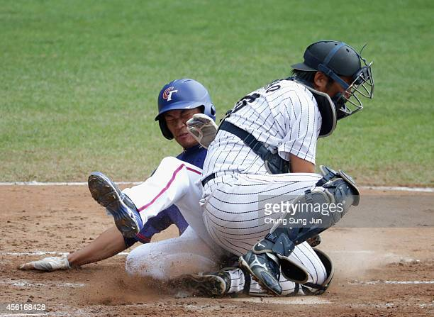 Wang Po Rong of Chinese Taipei slides into the home plate safe against Shigeki Nakano of Japan in the top of second inning during the Baseball...