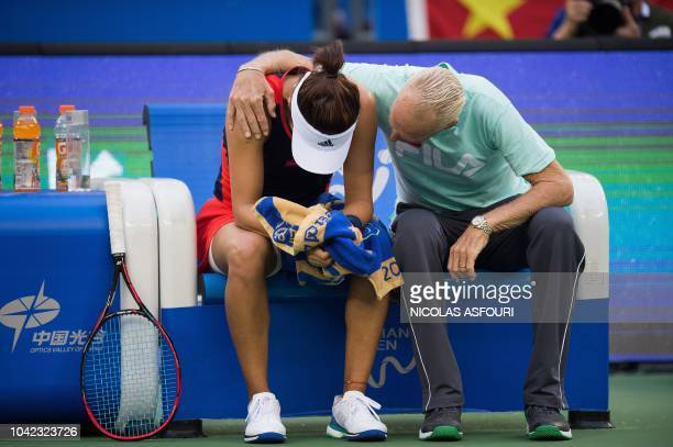 Wang Qiang of China is comforted by her coach Peter McNamara before retiring due to an injury while playing against Anett Kontaveit of Estonia during...