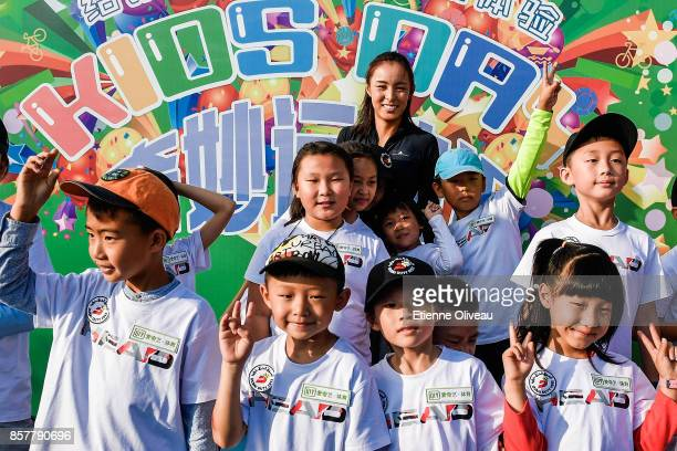 Wang Qiang of China poses for a picture with kids the iQiYi kids day on day six of the 2017 China Open at the China National Tennis Centre on October...