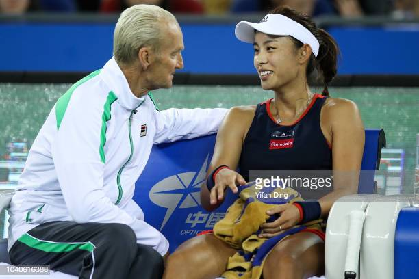 Wang Qiang of China smiles while talking with her coach Peter McNamara during their women's singles third round match against Daria Gavrilova of...
