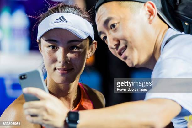 Wang Qiang of China takes selfie with fans after winning her women's singles first round match against Chang KaiChen of Taiwan during the Prudential...