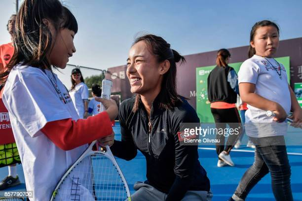 Wang Qiang of China talks with a kid during the iQiYi kids day on day six of the 2017 China Open at the China National Tennis Centre on October 5,...