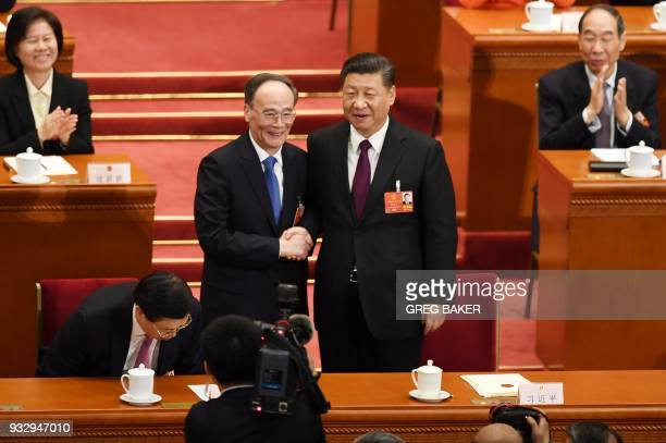 Wang Qishan former secretary of the Central Commission for Discipline Inspection shakes hands with China's President Xi Jinping as he is elected as...