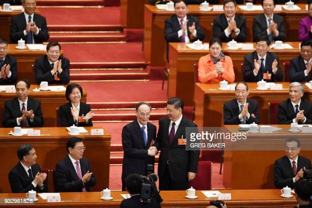 Wang Qishan former secretary of the Central Commission for Discipline Inspection shakes hands with China's President Xi Jinping after Wang was...