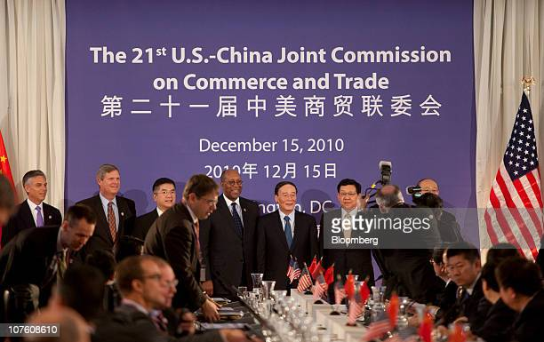 Wang Qishan vice premier of China center has his photograph taken with Ron Kirk US trade representative right to left Gary Locke US secretary of...
