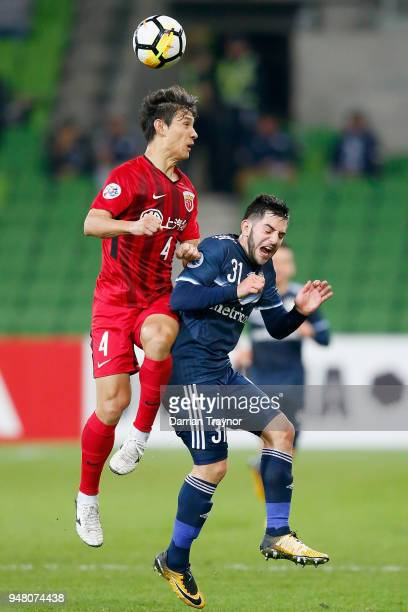Wang Shenchao of Shanghai heads the ball over Christian Theoharous of the Victory during the AFC Champions League match between Melbourne Victory and...