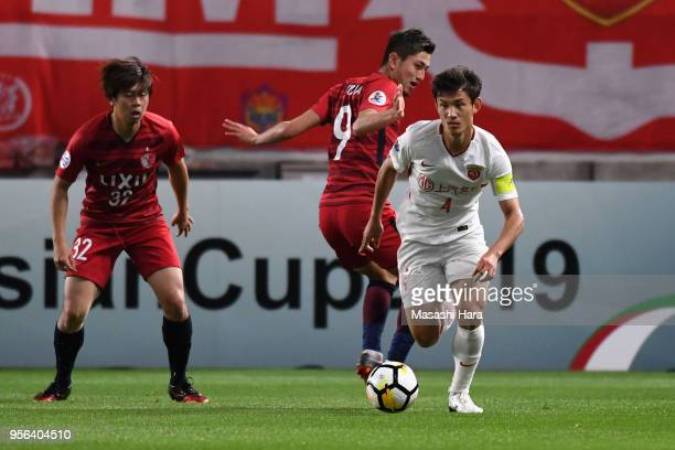 Wang Shenchao of Shanghai SIPG goes past Yuma Suzuki of Kashima Antlers during the AFC Champions League Round of 16 first leg match between Kashima...